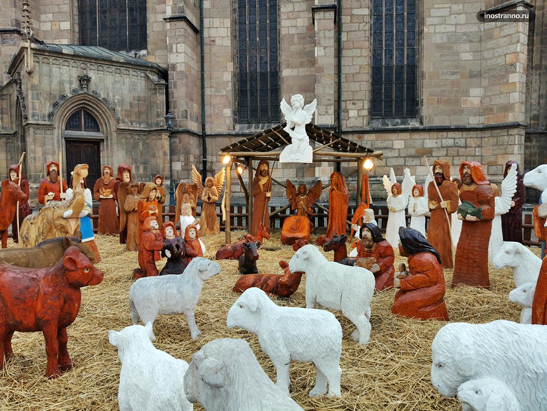 Вертеп на рождественском рынке с деревянными фигурами
